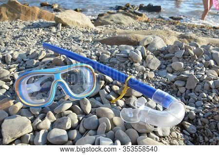 Diving. Mask And Snorkel For Scuba Diving Are On The Seashore, The Beach Is Stone. Diving With A Mas