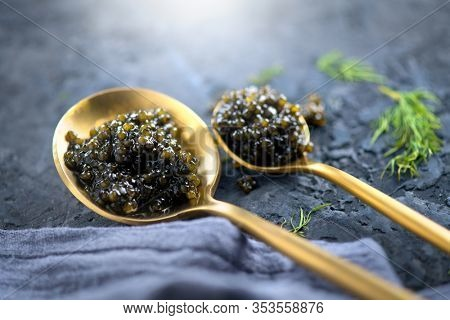 Black Caviar in a spoon on dark background. High quality real natural sturgeon black caviar close-up. Delicatessen. Texture of expensive luxury caviar. Food Backdrop.