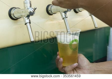 Bartender Pouring From Tap Fresh Beer Into The Plastic Cup. Hands Of Bartender Filling Beer Glass Fr