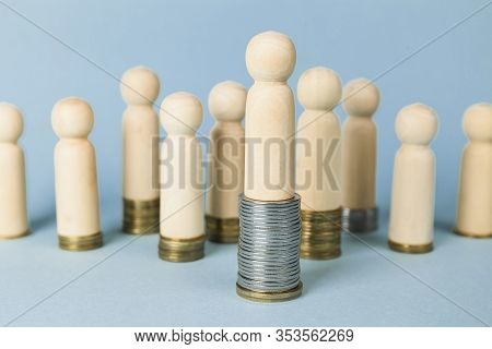 Wooden Figures On Stacks Of Coins, Concept Of Wealth And Poverty. Rising Or Falling Wages, Social In