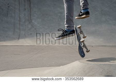 Vienna, Austria - 02/16/2020: Legs Of A Skateboarder Jumping With His Skateboard In Midair