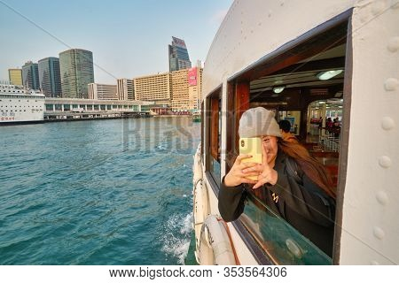 HONG KONG, CHINA - CIRCA JANUARY, 2019: woman on a Star Ferry crossing Victoria Harbour in Hong Kong. The Star Ferry is a passenger ferry service operator and tourist attraction in Hong Kong.