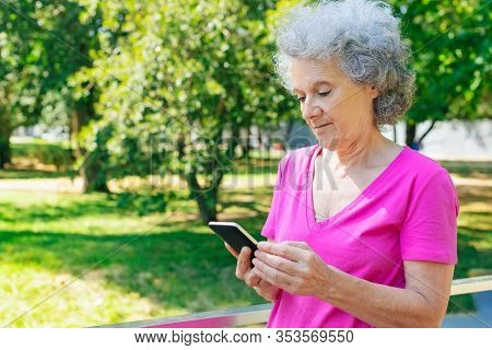 Focused Old Lady Checking Messages While Walking In Park. Senior Grey Haired Woman In Casual Standin