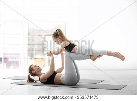 Mother And Daughter In Matching Sportswear Doing Yoga Together At Home