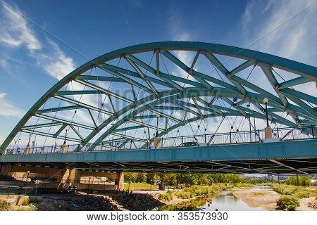 An Old Green Metal Bridge Over A River In Denver, Colorado