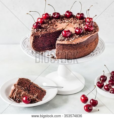 Sliced Chocolate Cake Decorated With Chocolate Shavings And Sweet Cherries, Square