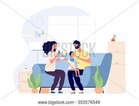 Parents And Baby. Feeding Infant, Happy Young Family Together. Mother Father And Toddler On Sofa Wit