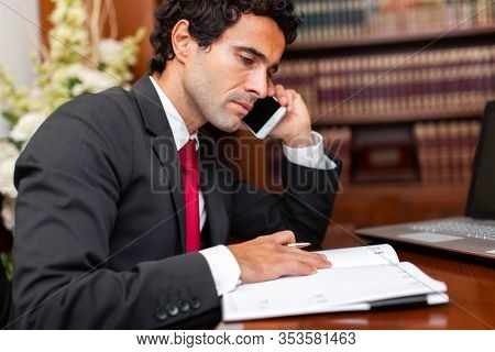 Lawyer reading a book and talking at the phone