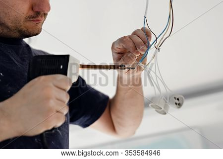 Electrician,a Male Electrician Is Standing On The Stairs Holding Wiring In His Hands And Stripping,r