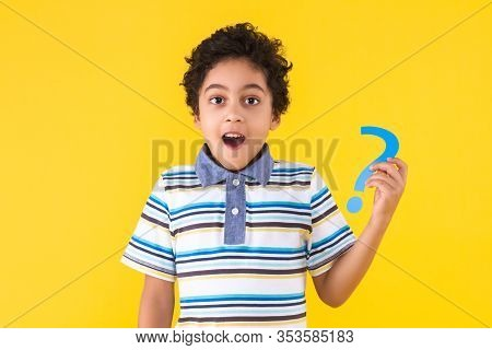 Curly Pretty Perplexed Dark Skinned Boy In Striped Blue T-shirt Is Holding In Hand Paper Question Si