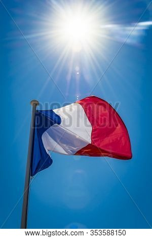 French Flag Backlit By Bright Sunshine On Riviera