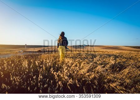 Beautiful woman on a meadow in late afternoon before the sun sets
