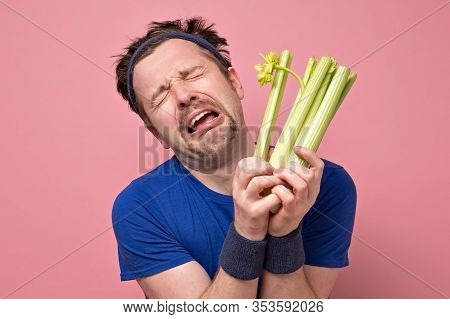 Man Holding Celery Crying. I Hate Vegetables But Should Eat For Healthy Diet.
