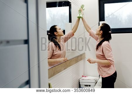 Young Housewife Washes A Mirror With Detergent,happy Woman Cleaning Mirror With Rag At Home,pretty W