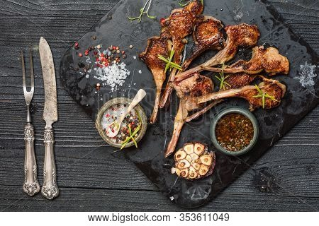 Grilling Lamb Chops With Salt, Pepper And Dry Herbs On Dark Stone Plate On Black Old Rustic Wooden T