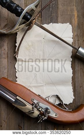 Vintage Pirate Epee And Pistol Lie On Empty Parchment On Wooden Background