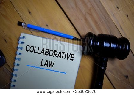 Collaborative Law Write On A Book Isolated On Wooden Background. Selective Focus On Text Collaborati