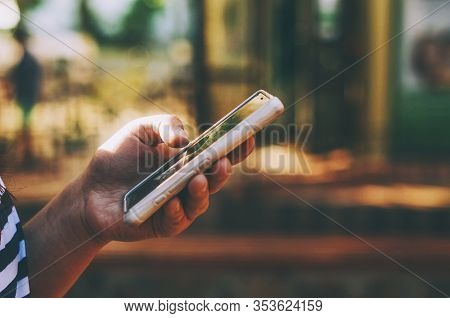 Girl With Mobile Cellphone In A Hand In Pink Cover Soft Focus Blurred Background