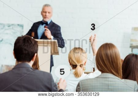 Selective Focus Of Buyer Showing Auction Paddle With Number Three To Auctioneer During Auction