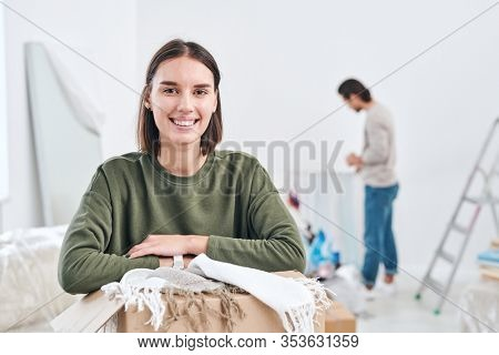 Happy young wife with toothy smile looking at you while unpacking boxes on background of man standing by wall