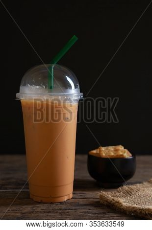 Still Life Ice Milk Tea On Wooden And Black Wood Background, Tea With Milk And Ice On Natural Wooden