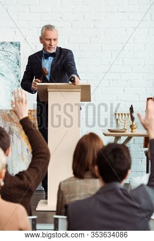 Selective Focus Of Auctioneer Holding Gavel And Pointing With Finger At Buyer During Auction