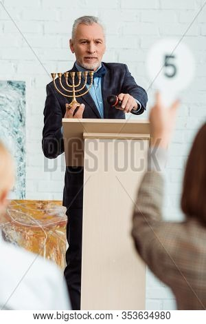 Selective Focus Of Auctioneer Looking At Buyer And Holding Candlestick During Auction