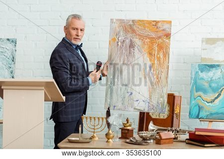 Auctioneer Talking With Microphone And Standing Near Picture During Auction
