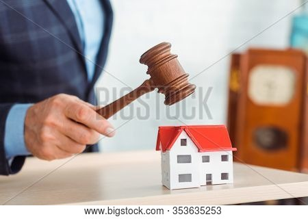 Cropped View Of Auctioneer Hitting Model Of House With Gavel During Auction