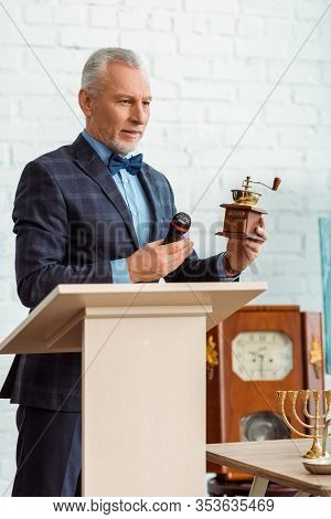 Handsome Auctioneer In Suit Pointing With Hand At Coffee Grinder And Holding Microphone During Aucti