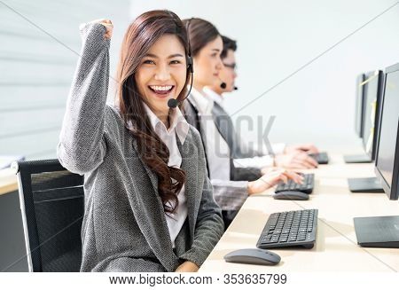 Young adult friendly and confidence operator woman agent smiling with headsets in call centre with her colleague team working as customer service and technical support workplace in background.