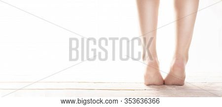 Female, Healthy Feet, Standing On Tiptoes On Wood Floor On A White Background, Wide View.