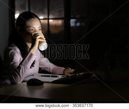 Young adult asian businesswoman drinking hot cofee while working late at night in her office with desktop computer. Using as hard working and working late concept.