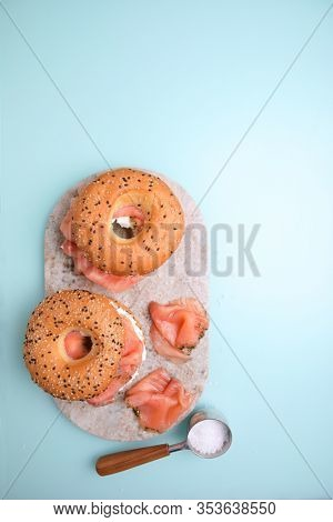 Bagels with cream cheese and salted salmon om a marble cutting board