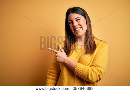 Young beautiful woman wearing casual sweater over yellow isolated background cheerful with a smile of face pointing with hand and finger up to the side with happy and natural expression on face