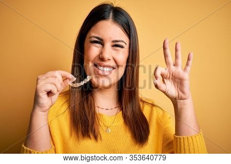 Young beautiful woman holding dental orthodontic aligner corrector over yellow background doing ok sign with fingers, excellent symbol