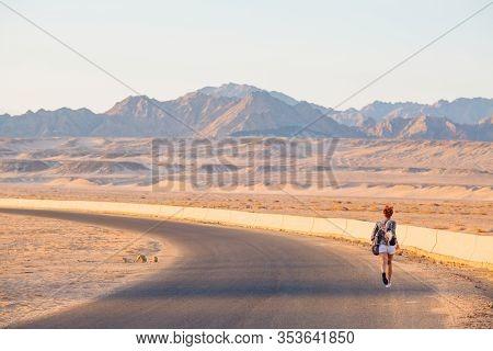 Near East. White Girl Running Away Along A Wide Desert Road
