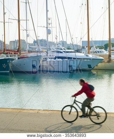 Man Riding Bicycle At Barcelona Port Vell. Motion Blur