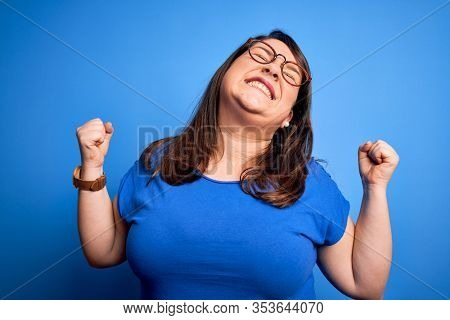 Beautiful brunette plus size woman wearing casual t-shirt over isolated blue background very happy and excited doing winner gesture with arms raised, smiling and screaming for success. Celebration