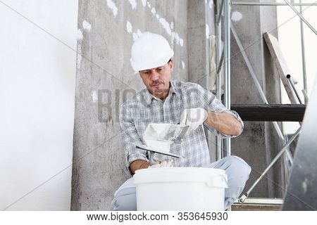 Plasterer Man At Work, Take The Mortar From The Bucket To Plastering The Wall Of Interior Constructi