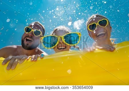 Family Having Fun On Summer Vacation. People Jumping In Swimming Pool. Active Lifestyle Concept. Spr