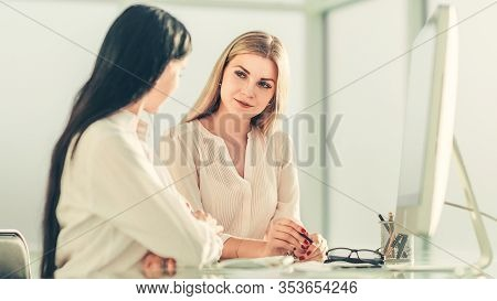 Two Employees Are Discussing Something Sitting At The Office Ta