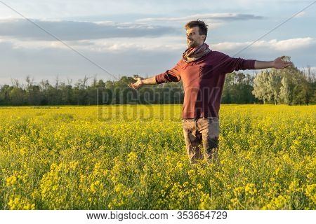 Happy Man With Opened Arms Standing In Yellow Rape Field. Guy Wide Opened Arms In Blooming Rape Fiel