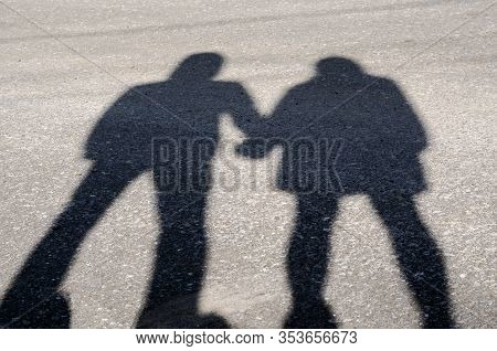 Series Of Silhouettes Of Young Lovers. Series 1. Shadow Of Lovers Hand In Hand At Sunset. A Guy And
