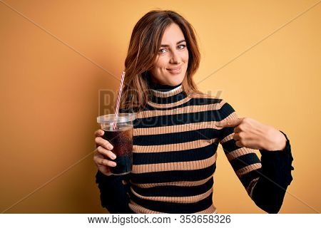 Young beautiful brunette woman drinking glass with cola refreshment using straw with surprise face pointing finger to himself