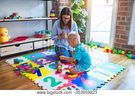 Young caucasian child playing at playschool with teacher. Mother and son playing with wooden pieces train at playroom