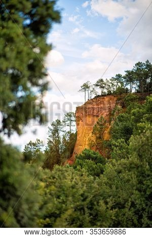Vertical Picture Of Hiking Path Ochre Trail In A Natural Colorful Area Of Orange Cliffs Surrounded B