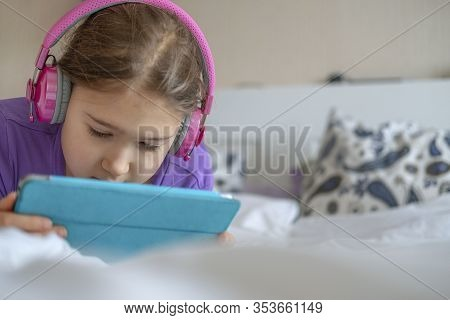 Young Teenager Girl In Pink Headphones With Tablet Device In Home Lying On Bed. Stock Photo For Any