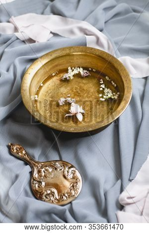 High Angle Of Brown Bowl Of Water With Fresh Small Flower Heads And Vintage Hand Mirror Among Delica
