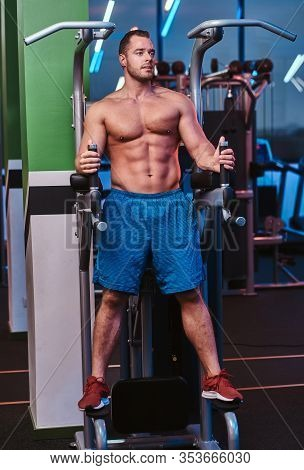 Full Height Portrait Of A Muscled Bodybuilder Standing On A Parallel Bars In A Modern Fitness Center